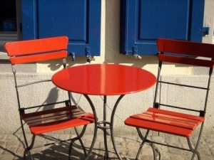 red table & chairs outside cafe on sunny day, social distancing, reopen,