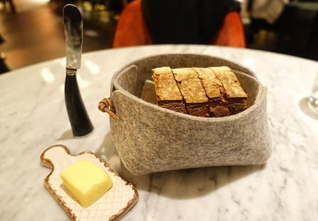 Caractere restaurant, felt bread basket with sourdough bread slices, butter pad, quirky cutlery knife