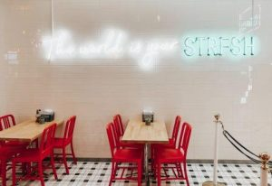 1960s empty cafe with formica tables, red chairs and neon sign inside