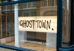 sign saying Ghost Town in empty city centre shop window, Good Hood store
