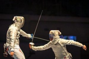 2 fencers parry and thrust, against black background