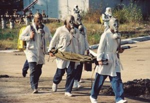men in white coats and gas masks carry away a victim on a stretcher