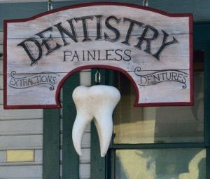 vintage dentist sign saying painless extractions and dentures with large mock tooth