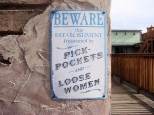 sign nailed to wall saying beware pickpockets and loose women