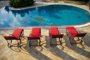 empty red sunbed by swimming pool on hot summer day