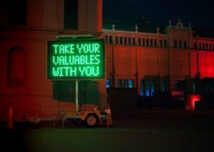 green neon sign saying Take Your Valuables With You, what is left is intatters