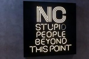 black board with white writing saying NO stupid people beyond this point, turning point marker, inept