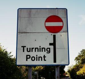 large white traffic sign saying Turning Point, U-turn