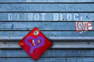purple heart on red square against blue metal background with Do Not Block Love