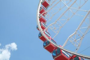 quarter section of ferris wheel red glass pods against blue sky, blue or red, turn continuously