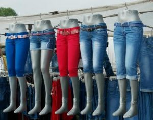 shop window mannequins wearing knee length jeans all blue but one red, groupthink