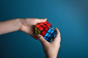 hands solving rubiks cube puzzle, rotating red and blue squares, emphasis