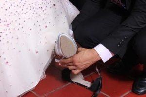 bridegroom fitting bride's shoe on her foot
